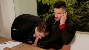 Sam Decker is on the phone talking to a client, while Dom is scrolling thru social media pages. Dom approaches Sam and starts massaging Sam's shoulders.